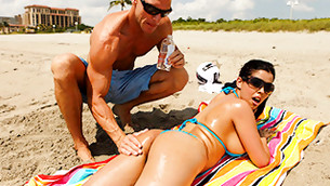 Strong muscular dude oils his naughty girl's ass o the beach