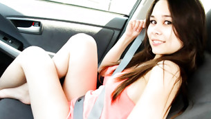 Brunette astonishing lady is posturing in short clothes in the car